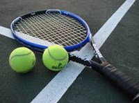 tennis racket and tennis balls laying on a tennis court